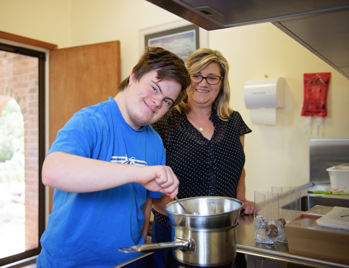 20-year-old NDIS participant Ben, stirring a pot on the stove with his mum behind him overseeing his progress.