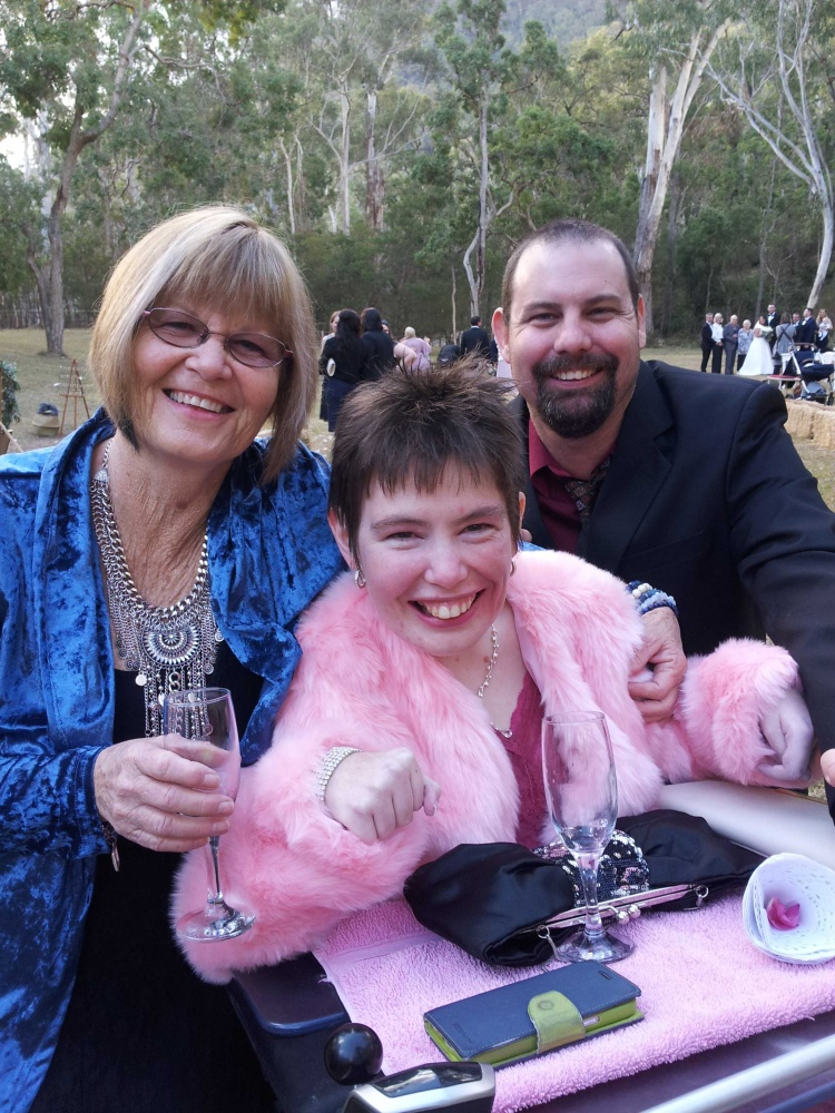 Lacey and her parents at an outdoor wedding, they are dressed up, Lacey has a champagne glass in front of her