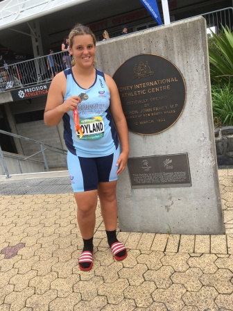 Rosie stands in front of the sydney international athletic centre with her medal