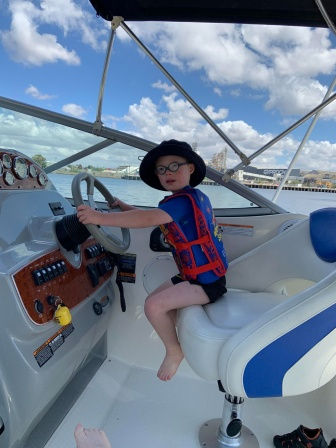 William sits in the captains seat on his parents boat