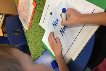 Looking over the shoulder of a six-year-old NDIS participant, utilising Early Childhood Early Intervention supports through his NDIS plan, practicing to write his name.