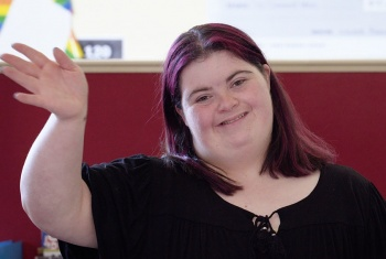 NDIS participant Victoria smiling and waving at the camera