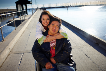 Male NDIS participant on a pier in a wheelchair. His wife is standing behind him with her arms wrapped around him. Both are smiling at the camera.