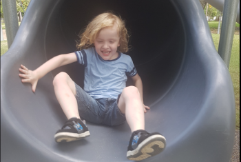 Young male NDIS participant coming down an enclosed slide smiling.