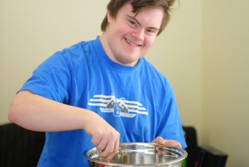 Self-employed 20-year-old in a blue t-shirt, smiling at the camera, using a spoon to mix a cake in a stainless steel mixing bowl.