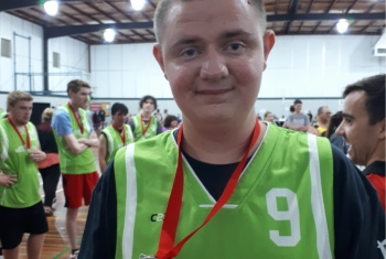 NDIS participant James is wearing a green jersey with the number nine on it. It's part of his pool playing competition uniform. He is proudly wearing a medal around his neck. He is smiling at the camera.