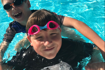 Young male NDIS participant in a pool, wearing pink goggles. Another young male is behind him in the pool with his arms around him. Both are smiling at the camera.