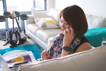 Female NDIS participant in her 20's using her mobile phone and laptop while sitting on a couch, and an NDIS brochure by her side.