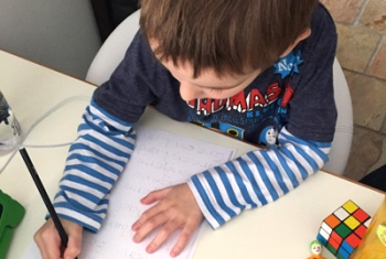 Looking over the top of a six-year-old male NDIS participant and ECEI recipient, practising to write his name at a desk.