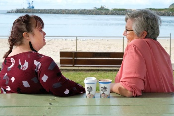 Two women, one with disability, sitting on a park bench at the beach enjoying the view, a chat and a coffee.