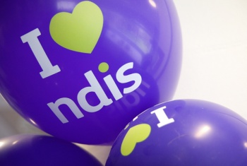A close-up of three purple I love NDIS balloons