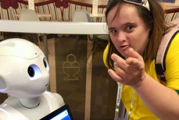 Shona interacts with a robot, she points toward the camera