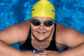 Ruby, in a yellow swimming cap and goggles, is in the pool, her arms folded on the edge, smiling at the camera