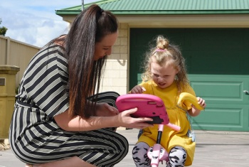 Sophia and her mum play outside, while Sophia communicates using the new device.