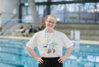Lily stands in front of the pool with her swimming medals