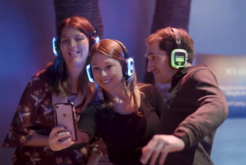 Gig Buddy participants and volunteers smile for a group selfie wearin neon silent disco headphones