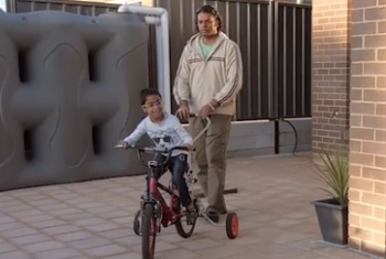 Ram enjoys riding his bike in his yard at home with his dad's help