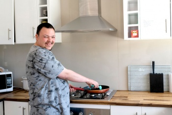 Christopher happily using newly found skill of cooking on his stove in his share house kitchen