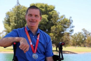 Chris sits in his wheelchair wearing his Sailability Championship medal