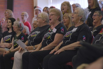 Members of the With One Voice choir sing from their chairs