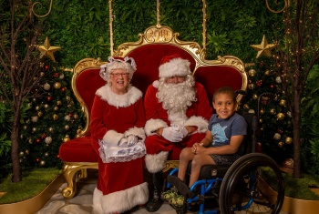 Caelin sits in his chair next to Santa and Mrs Claus