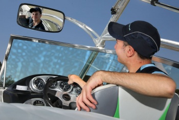 Stefan sits in the driver's seat of his speedboat and looks into the mirror
