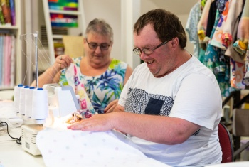 Steven is wearing a white t-shirt and sitting at a sewing machine. A woman in a brightly coloured t-shirt is sitting next to him