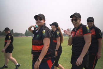 The women at the National Cricket Inclusion Championships wave at the camera as they walk onto the ground in their uniforms