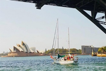 A yacht sails under the Sydney Harbour Bridge, the Sydney Opera House is in the distance